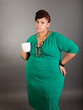 Plus sized business woman. Plus sized african american business woman wearing a green dress holding a white ceramic coffee or tea cup on a grey background Royalty Free Stock Photos