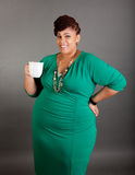 Plus sized business woman. Plus sized african american business woman wearing a green dress holding a white ceramic coffee or tea cup on a grey background Stock Image
