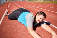 Bad luck. Plus-sized female fallen down racetrack during hurdle marathon Royalty Free Stock Image