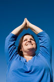 Plus Sized Fitness- Yoga. Beautiful plus-sized woman doing yoga outdoors against vivid blue sky Stock Photo