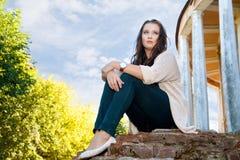 Plus wielkościowa dziewczyna siedzi na starym ściana z cegieł Obrazy Stock