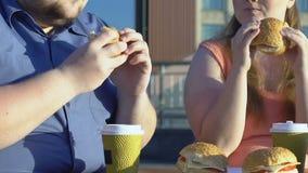 Plus wielkościowa para je kaloria hamburgery w ulicznej kawiarni, otyłość problem zbiory
