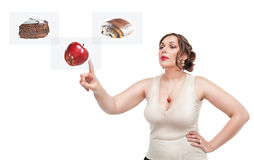 Plus wielkościowa kobieta robi wyborowi między zdrowym i niezdrowym jedzeniem Zdjęcie Stock