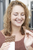Plusgrößen-Frau, die Schokolade essend genießt Stockfotografie