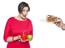 Plusgrößenfrau, die Wahl zwischen gesundem und ungesundem Lebensmittel trifft Stockfotos