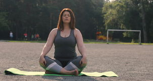 Plusgrößenmädchen, das draußen Yoga meditiert stock footage