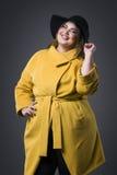 Plusgrößenmode-modell im gelben Mantel und im schwarzen Hut, fette Frau auf grauem Hintergrund, überladener weiblicher Körper Stockfoto