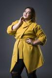 Plusgrößenmode-modell im gelben Mantel und im schwarzen Hut, fette Frau auf grauem Hintergrund, überladener weiblicher Körper stockfotografie