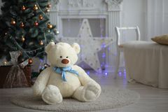 Plush bear on a light carpet on the background of a Christmas tree royalty free stock photos