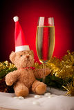 Plush bear with glass of sparkling wine on christmas decoration Royalty Free Stock Images