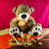 Plush bear with a glass vase and a spoon for honey and nuts. Plush bear with a vase and a spoon for honey and nuts stock photography