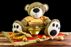 Plush bear with a glass vase and a spoon for honey and nuts. Plush bear with a vase and a spoon for honey and nuts stock photo