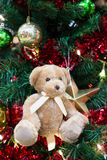 Plush bear with ornaments and Christmas tree background Stock Photo