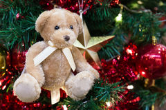 Plush bear with ornaments and Christmas tree background Stock Photography