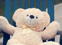 Plush bear relaxed in chair. A plush bear sitting in chair with arms stretched out. Retro/vintage Royalty Free Stock Photo