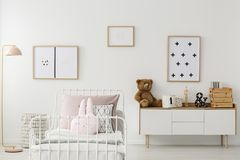 Kid`s bedroom interior with mockup. Plush bear on white cupboard against the wall with posters in kid`s bedroom interior with mockup stock photo