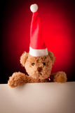 Plush bear with with white text card on red christmas background Stock Image