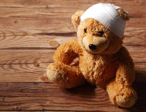 Plush Brown Teddy Bear with Bandaged on the Table Stock Image