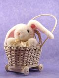 Plush bunny in wicker pram. Plush bunny rabbit toy in an antique baby pram against lavender fabric Royalty Free Stock Photography