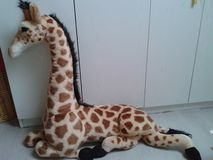 Plush giraffe in a white baby room stock images