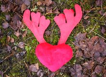 Plush heart with antler on brown leaves. royalty free stock photo