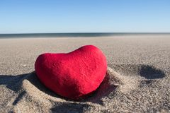 Plush heart on the sand under the scorching sun. Stock Images