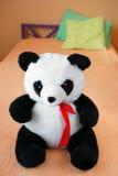 Plush Panda Bear sitting on a Bed Stock Photos