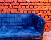 Plush puff blue sofa on a brick backgrund vintage industrial style. Indoor concept royalty free stock photography