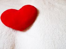 Plush heart on white wool blanket. Plush red heart on white wool blanket royalty free stock photos