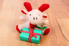 Plush reindeer with gift for Christmas or other celebration Royalty Free Stock Photo