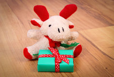 Plush reindeer with gift for Christmas or other celebration Stock Photos