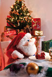 Plush Santa Claus sitting at table, christmas tree Royalty Free Stock Photos