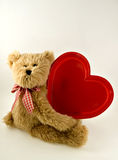 Plush Teddy Bear with Big Red Heart. Light brown plush teddy bear with plaid bow and large red heart Stock Image