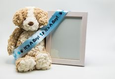 Plush teddy bear and empty picture frame with `It`s A Boy` ribbon royalty free stock images