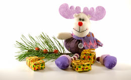Plush toy deer sitting near the branch and gifts. Plush toy deer sitting near the spruce branch with christmas balls and gift boxes. White background with soft Royalty Free Stock Images
