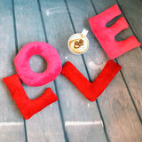 Plush toy letters L O V E and a cup of cappuccino with hearts. Top view to a composition of plush letters and and cappuccino cup placed over blue wooden floor Royalty Free Stock Photography