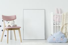 Plush toy on pink chair and blue pillow in child`s room interior stock image