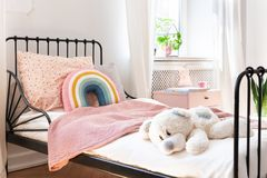 Plush toy, rainbow pillow and pink blanket stock images