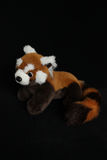 A plush toy in the shape of a red panda on a black background Royalty Free Stock Photo