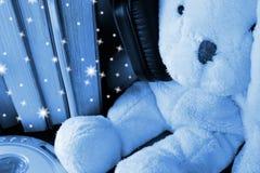 Plush toy wearing too big headphones sitting among standing books. Blue night star effect stock photo