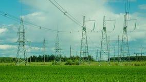 Plusieurs appuis de ligne électrique sont à l'arrière-plan des nuages mobiles banque de vidéos