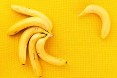 Plusieurs bananes mûres jaunes des tropiques sur un tissu jaune Images stock