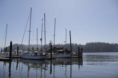 Plusieurs bateaux accouplés dans la baie avec des montagnes Images stock