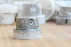 Plusieurs becs de plastique d'un pulvérisateur de peinture qui se trouvent sur une surface en bois sur un fond gris de mur Les ch Photographie stock
