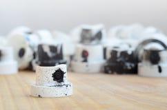 Plusieurs becs de plastique d'un pulvérisateur de peinture qui se trouvent sur une surface en bois sur un fond gris de mur Les ch Photos stock
