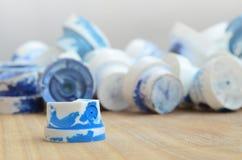 Plusieurs becs de plastique d'un pulvérisateur de peinture qui se trouvent sur une surface en bois sur un fond gris de mur Les ch Images libres de droits