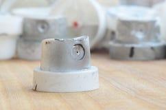 Plusieurs becs de plastique d'un pulvérisateur de peinture qui se trouvent sur une surface en bois sur un fond gris de mur Les ch Images stock
