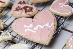 Plusieurs biscuits de vacances de Valentine de coeur dans le givrage rose avec dessus Photographie stock libre de droits