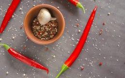 Plusieurs bols ronds brûlants de poivrons rouges avec des épices dans une table foncée Images stock