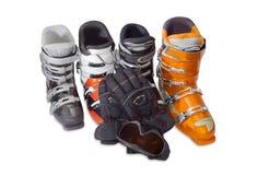 Plusieurs bottes de ski, lunettes de ski et gant alpins de ski Images stock